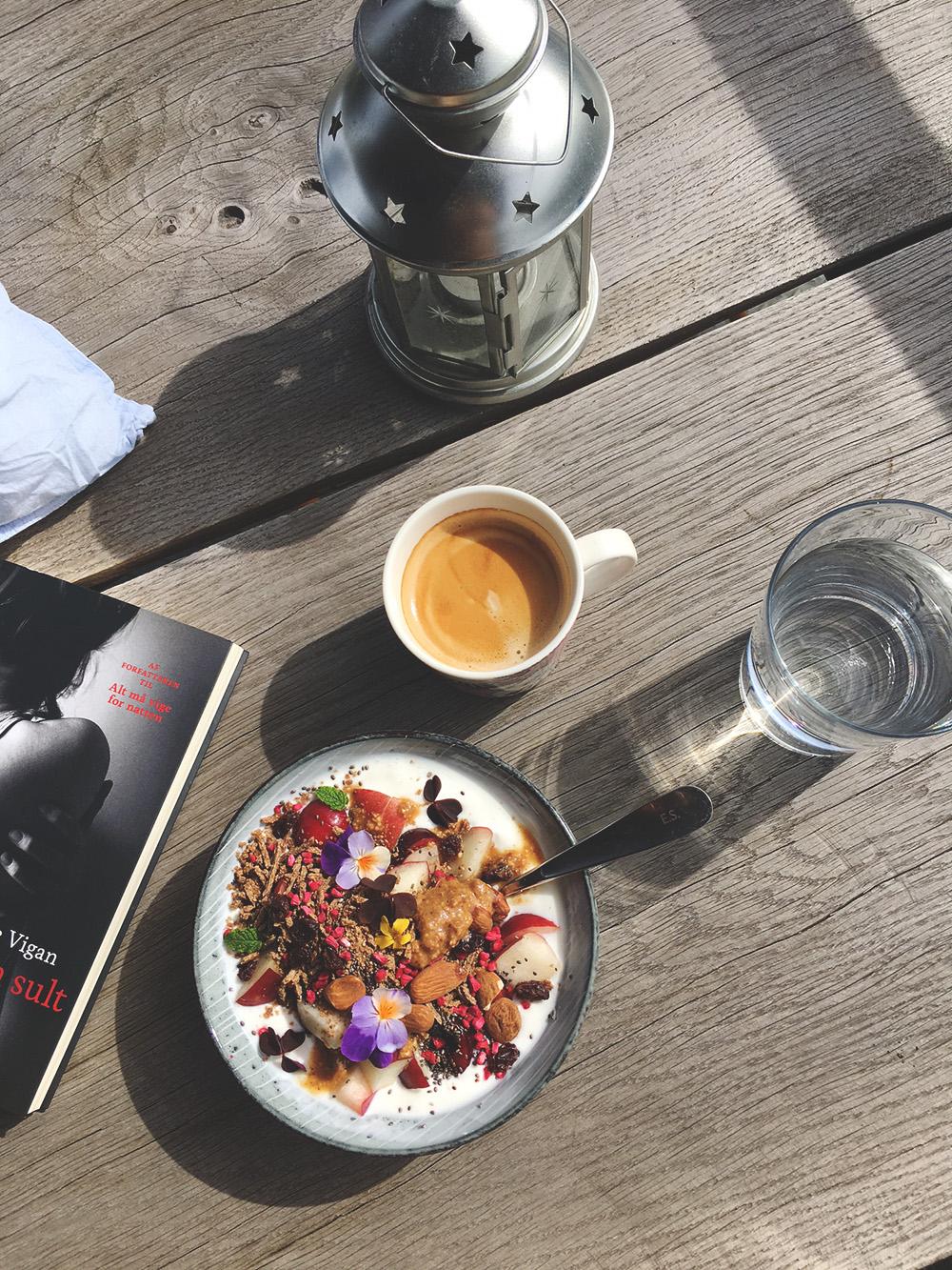 morgenmad på altanen, kaffe, yoghurt med granola og frugt, bog