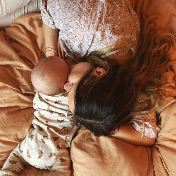 baby og mor ligger på sengen