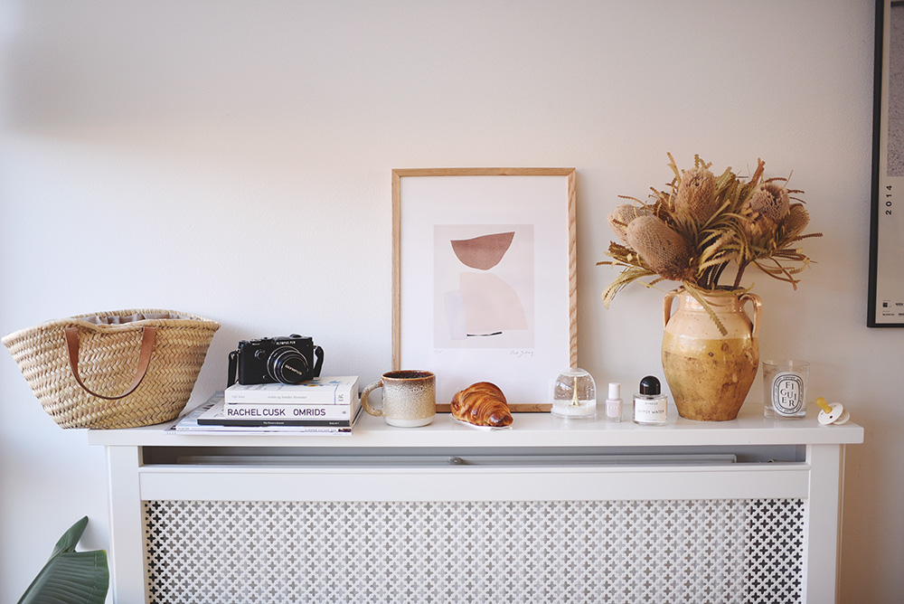 stilleben med kurv, kamera, kop, croissant, vase m.m.