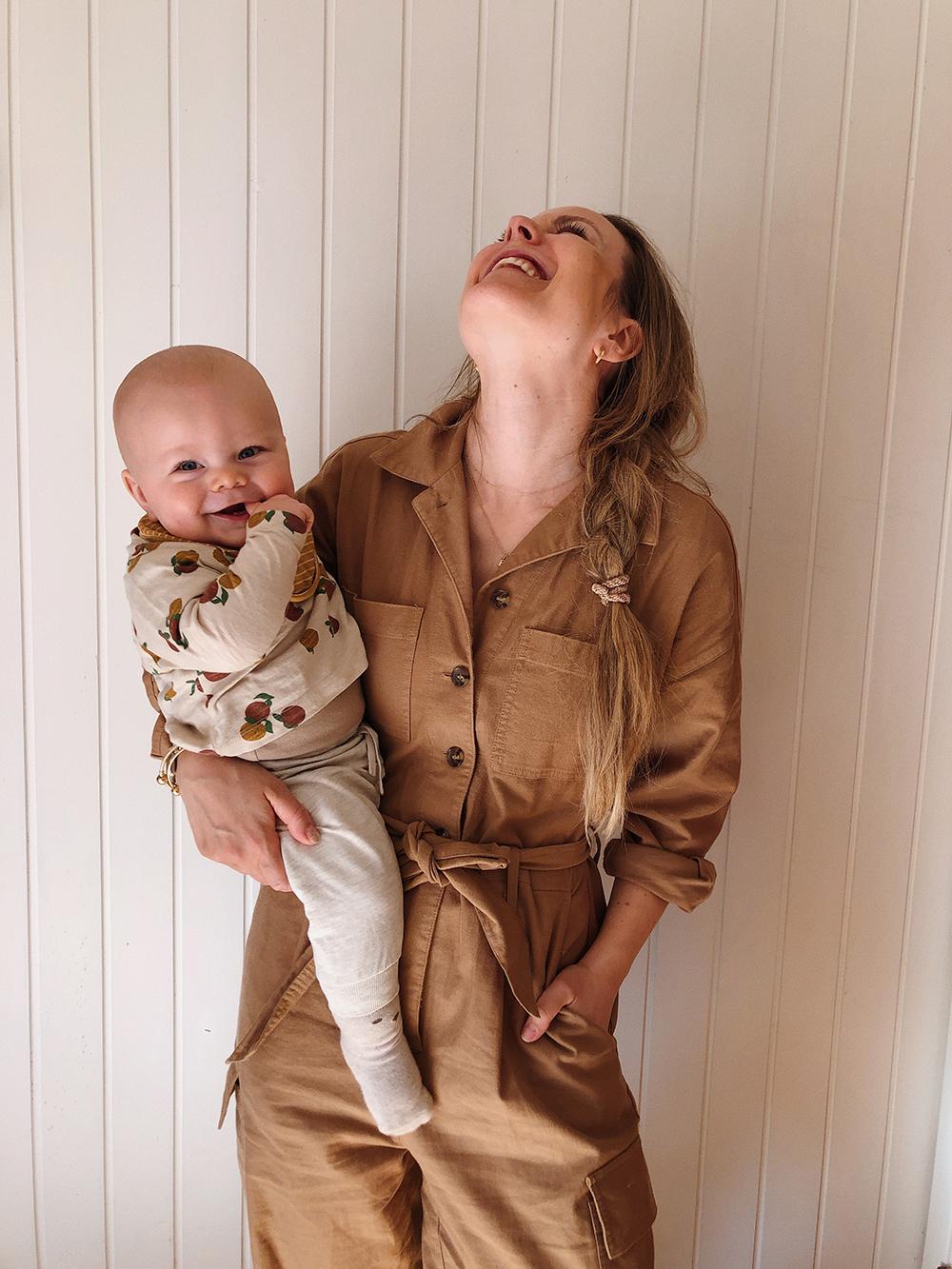 mor med baby på armen, begge smiler stort
