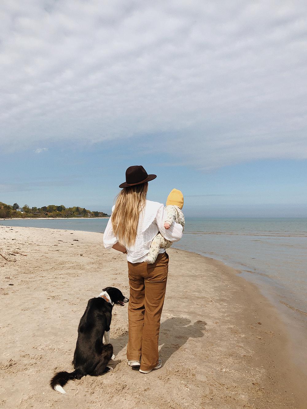 mor med barn og hund på strand