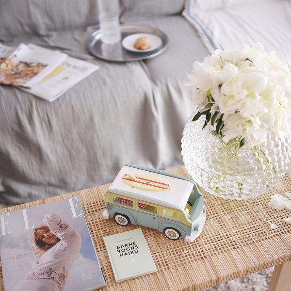 bord med blomster i vase, digtsamling og legetøjs-autocamper